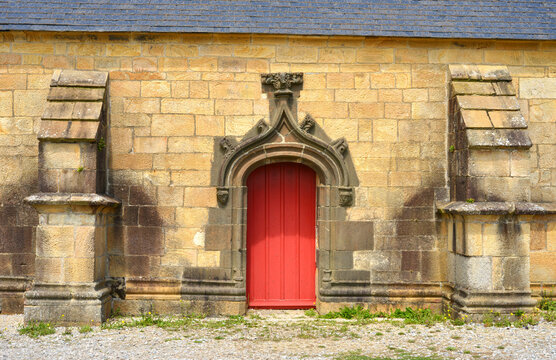 Little red entry door to a chapel, colorful stones in Brittany, Europe