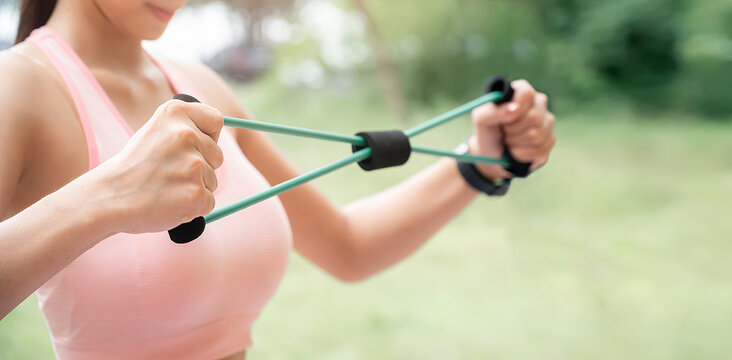 Closeup shot of fitness woman workout with resistance band for the muscles of the chest.