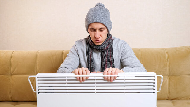 Sad young man with scarf and knitted hat warms hands above heater, sitting on modern soft sofa in living room in cold winter without central heating