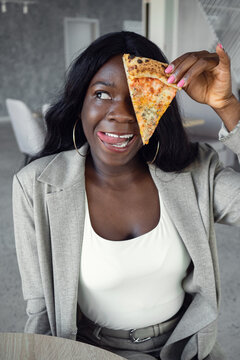 african american woman in business suit smiling covering eye with slice of pizza.