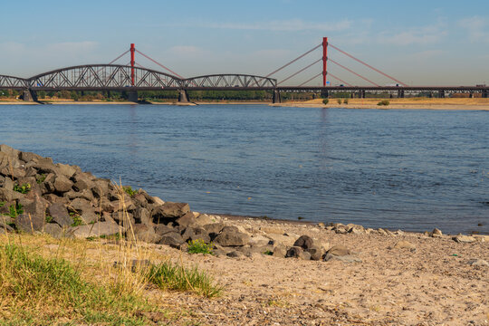 Duisburg, North Rhine-Westfalia, Germany - August 07, 2018: A parched meadow at the River Rhine with the Beeckerwerther Bridge and the Haus-Knipp Railway bridge in the background