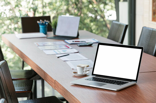 Blank screen laptop computer on wooden table in meeting room.