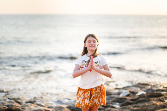 Cute caucasian child preteen girl with hands by the stones by the sea, boat trips, vacation and freedom, childhood by the sea, warm toning