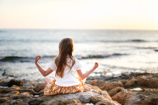 Cute caucasian child girl with long hair meditates by the sea, silence and calmness, warm toning