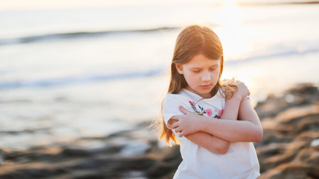 Sad Lonely Caucasian child preteen girl hugs herself with her arms by the sea, toning, negative emotions, emptiness and sadness, calmness and self-focus