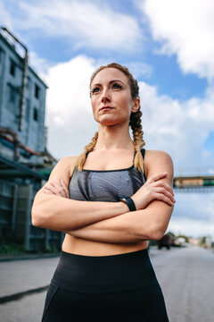 Sporty woman with crossed arms posing in front of a factory in an industrial zone