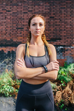 Sportswoman with crossed arms looking camera posing in front of a brick wall