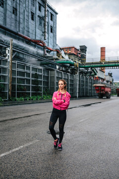Sporty woman posing in front of a factory in an industrial zone