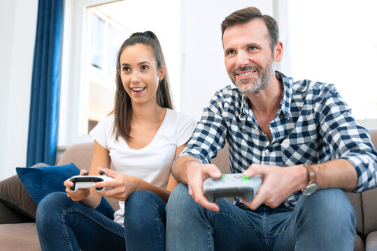 Couple playing games on console, gamepad in hands