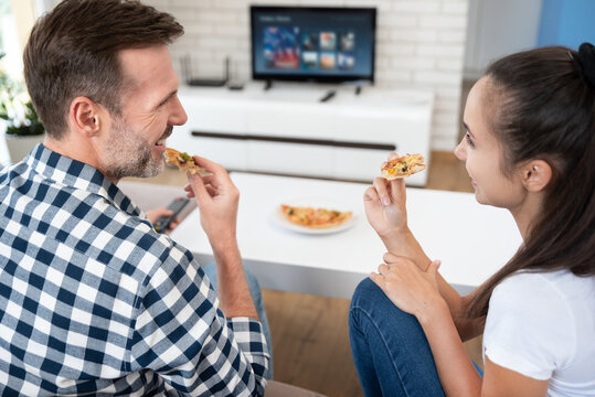 Couple watching TV while eating pizza