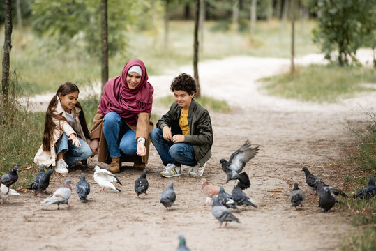 Muslim family feeding doves in park