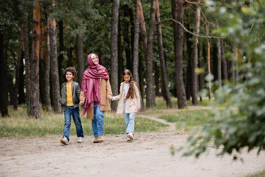 Arabian mother and kids walking in park