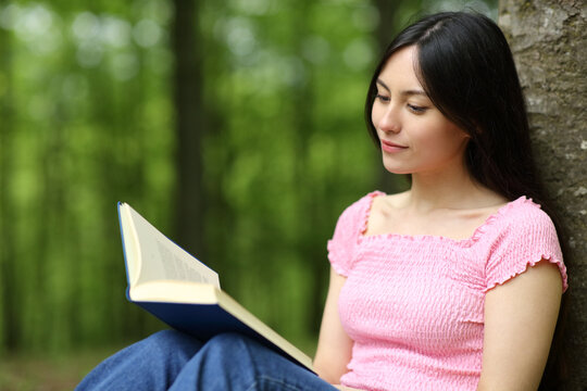 Asian woman reading paper book in a park