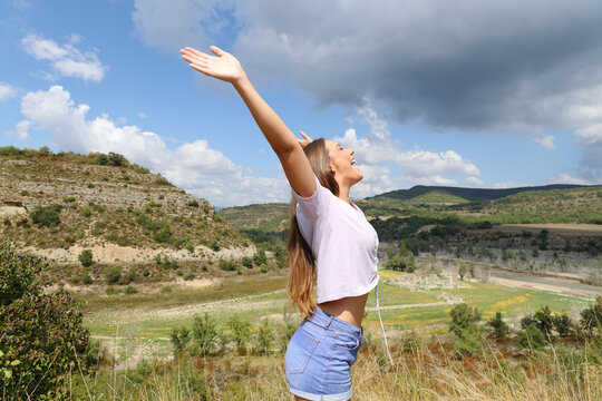 Euphoric woman outstretching arms in the mountain celebrating