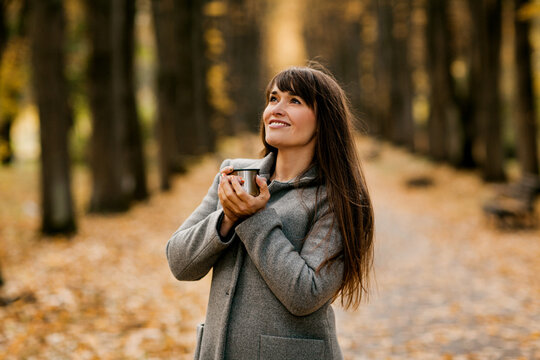 Portrait of a beautiful young woman drinking a hot drink while walking in an autumn park