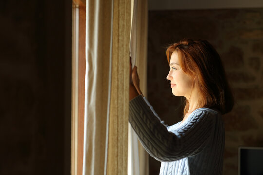 Satisfied woman opening curtains at home