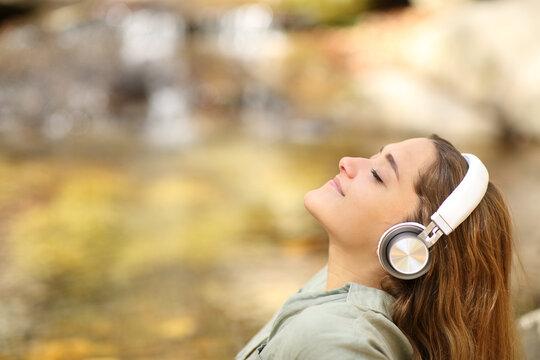 Woman breathing fresh air listening to music