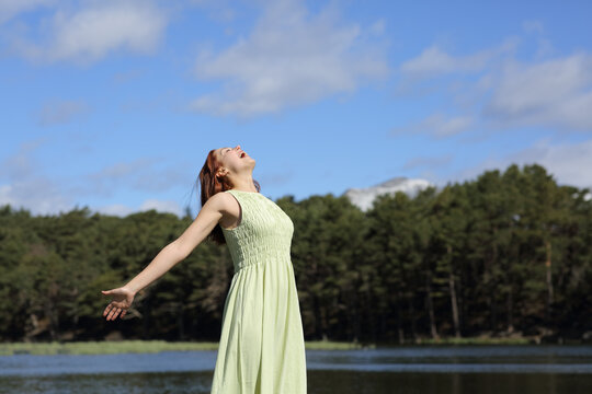 Woman in green stretching arms screaming in a lake