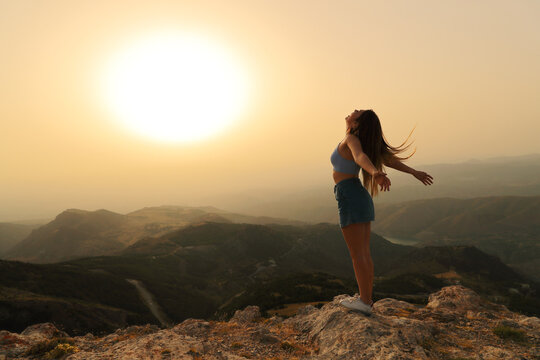 Woman celebrating breathing and stretching arms at sunset