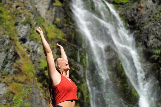 Woman raising arms in a waterfall celebrating holiday