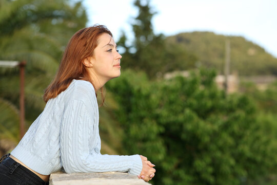 Woman contemplating views from balcony of rural house