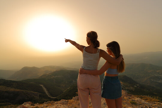 Women pointing at sunset in the mountain