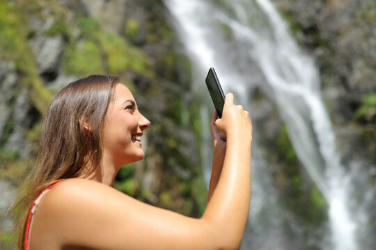 Woman taking photos with smartphone in a waterfall