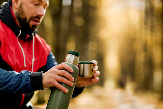 Close-ups of a man pouring tea into a cup from a thermos while relaxing in an autumn park or forest