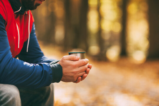 Close-up of a man's hands with a cup of hot drink in an autumn park or forest