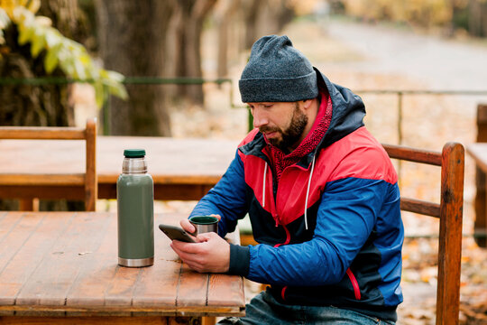 A young man using a mobile phone is sitting outdoors in a cafe or restaurant on an autumn day, drinking a hot drink, resting while walking