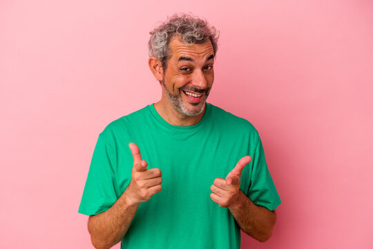 Middle age caucasian man isolated on pink background  pointing to front with fingers.
