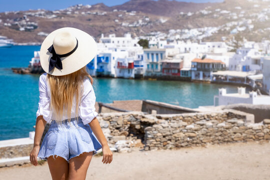 Backview of a blonde tourist woman who looks at the beautiful town of Mykonos island, Greece, during her summer holidays