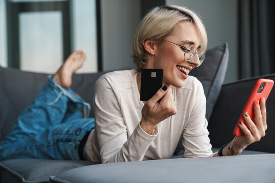 Smiling blonde mid aged woman shopping online
