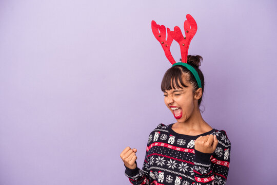Young mixed race woman with reindeer hat celebrating Christmas isolated on purple background  raising fist after a victory, winner concept.