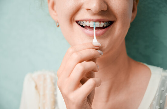 Close up of woman using elastic cleaning toothpick while brushing teeth with orthodontic brackets. Woman cleaning teeth with dental floss brush. Concept of dentistry, hygiene and dental care.