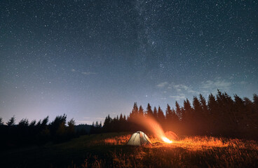 Fototapeta Night camping under amazing starry sky. Wide angle view on beautiful landscape in mountains. Two tourist tents and campfire, wall of spruces on background. Concept of travelling and astrophotography obraz