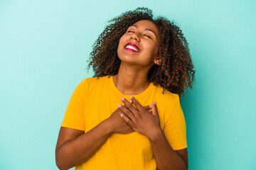 Obraz Young african american woman with curly hair isolated on blue background laughing keeping hands on heart, concept of happiness. - fototapety do salonu