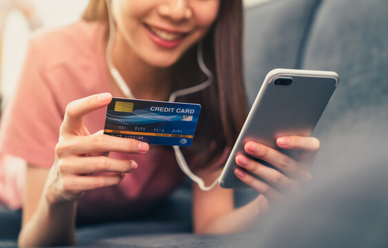 Happy young Asian woman holding credit card and using smartphone for shopping online with payment on internet banking.