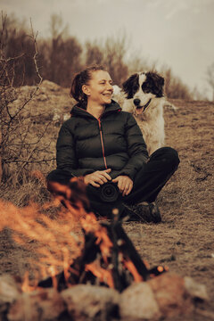 Young woman tourist hugging her dog outdoors while hiking with her best friend.