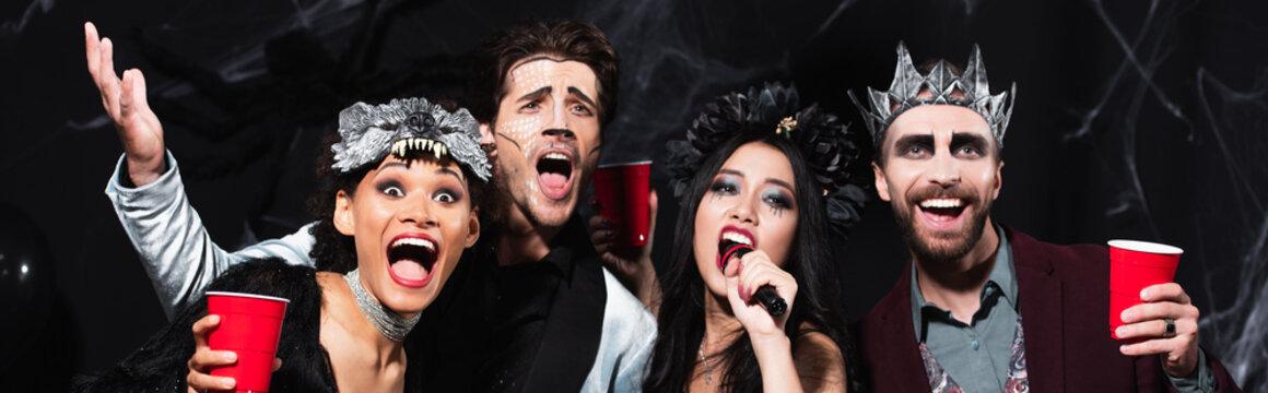 man in halloween makeup gesturing while singing karaoke with multiethnic friends on black, banner