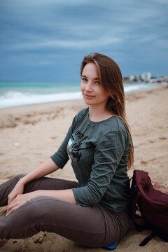 woman enjoying sea air on autumn beach before thunderstorm