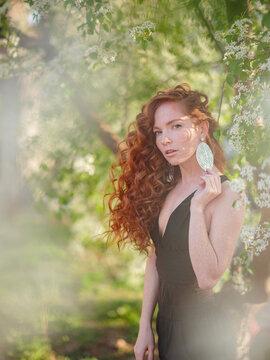 Redhead woman in black suit walks in spring city