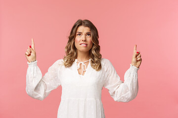 Obraz Skeptical and embarrassed blond caucasian woman in white cute dress, grimacing, cringe from seeing something disgusting, frowning doubtful and pointing fingers up strange thing, pink background - fototapety do salonu