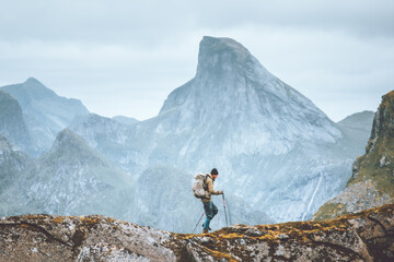 Fototapeta Man hiking in mountains traveling solo with backpack outdoor active vacations in Norway healthy lifestyle extreme sports obraz