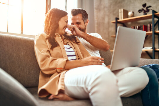Young couple in love are sitting on the couch with a laptop at home. A married couple are relaxing and having fun in the living room. Online shopping, work from home.