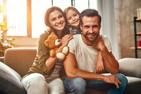 Happy dad and mom with their cute daughter and teddy bear hug and have fun sitting on the sofa in the living room at home.
