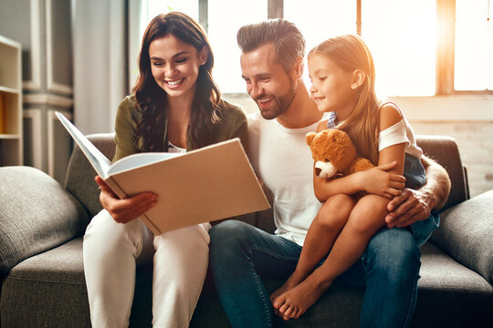 Happy dad and mom with their cute daughter and teddy bear are reading a book while sitting on the sofa in the living room at home.