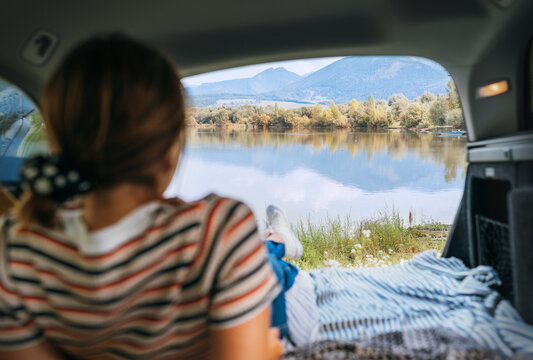 Woman lying in the cozy car trunk and enjoying the mountain lake view in the morning after the camper night. Warm early autumn auto traveling concept image.
