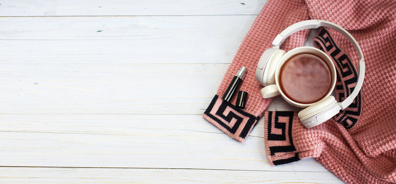Cozy winter morning .Hot tea or coffee, knitted sweater, perfume and headphones on wooden background . banner