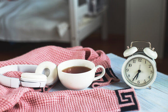 A cup of hot tea, knitted sweater, alarm clock and headphones in the bedroom. winter morning concept